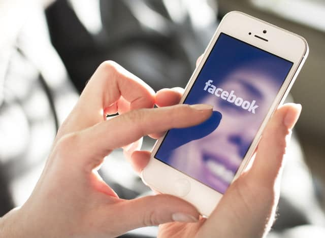 a person logging into facebook on their mobile device